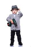 De jongen die van de baby een hoed draagt die een elektroboor houdt Stock Foto's
