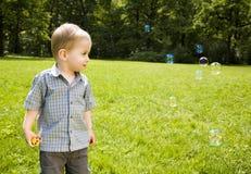 De Jongen die van de baby op Zeepbels kijkt Stock Foto's