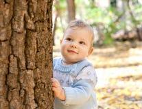 De jongen die van de baby zich dichtbij boom in de herfstpark bevindt Royalty-vrije Stock Foto's