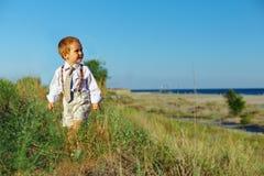 De jongen die van de bedrijfsstijlbaby het gebied loopt dichtbij overzees stock afbeeldingen