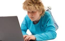 De jongen die van de blonde met laptop werkt stock afbeelding