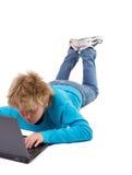 De jongen die van de blonde met laptop werkt stock foto's
