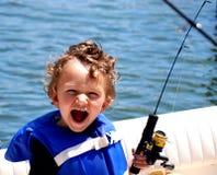 De Jongen die van de peuter op een boot vist Stock Afbeeldingen