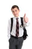 De jongen die van de school duimen op handteken toont stock afbeeldingen