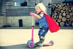 De Jongen die van de Superherobaby Autoped Aanbiddelijk Concept hanteren Royalty-vrije Stock Afbeeldingen