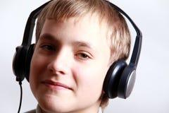 De Jongen die van de tiener aan hoofdtelefoons luistert Stock Foto