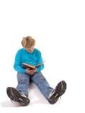 De jongen die van de tiener een boek leest stock foto's