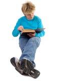 De jongen die van de tiener een boek leest stock foto