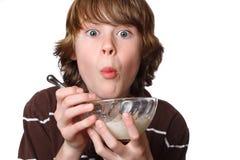De jongen die van de tiener een kom graangewas eet royalty-vrije stock foto