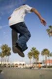 De Jongen die van de tiener het Springen met een skateboard rijdt Stock Afbeeldingen