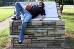 De Jongen die van de tiener na het Spel van het Basketbal rust stock foto's
