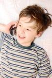 De jongen die van de tiener op celtelefoon spreekt Stock Fotografie