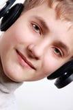 De Jongen die van de Tiener van het portret aan hoofdtelefoons luistert Stock Afbeelding