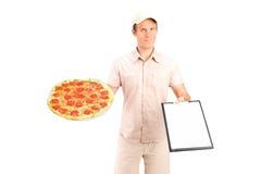 De jongen die van Dlivery met klembord een pizza levert Royalty-vrije Stock Afbeelding