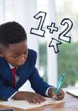 De jongen die van het bureaujonge geitje met onderwijspictogrammen schrijven Stock Foto