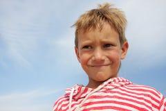 De jongen die van het kind gezichten over hemelachtergrond maakt Stock Fotografie