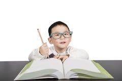De jongen die van het schoolkind in glazen boek bestuderen Royalty-vrije Stock Foto