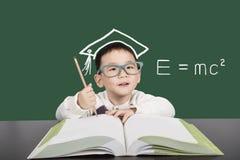 De jongen die van het schoolkind in glazen boek bestuderen Stock Foto's