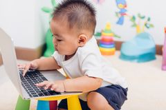 De jongen die van de kindbaby gebruikend laptop computer werken stock fotografie