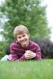 De jongen die van Preteen in gras glimlacht Stock Foto's