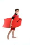De jongen die van Surfer een bodyboard houdt Stock Afbeelding