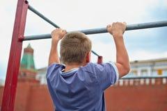 De jongen doet kin-UPS tegen de muur van het Kremlin Royalty-vrije Stock Foto's