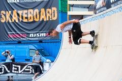 De jongen doet trucs met het skateboard op een helling royalty-vrije stock fotografie
