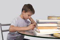 De jongen doet zijn thuiswerk met een in hand pen Stock Afbeelding