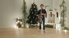 De jongen in donkere jeans en overhemd die de saxofoon in de ruimte met de Kerstmisatmosfeer spelen, decoratie stock video
