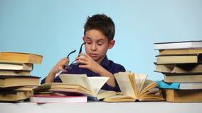 De jongen draagt glazen en het doorbladeren door het boek Achtergrond voor een uitnodigingskaart of een gelukwens Langzame Motie stock footage