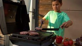 De jongen draait de kotelet op de grill stock video