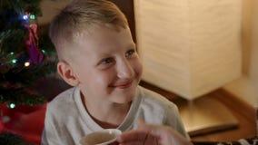 De jongen drinkt hete chocolade en krijgt chocoladesnor stock footage