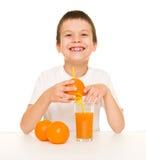 De jongen drinkt jus d'orange met een stro Stock Afbeeldingen