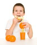 De jongen drinkt jus d'orange met een stro Stock Foto's