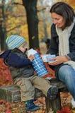 De jongen drinkt thee van een thermosfles met haar moeder Stock Foto