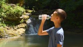 De jongen drinkt water van fles dichtbij waterval stock footage