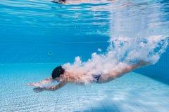 De jongen duikt in zwembad stock foto's