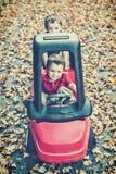 De jongen duwt zijn Broer in Toy Car Outside Stock Afbeeldingen