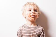De jongen eated chocolade, grappig vuil geglimlacht gezicht royalty-vrije stock fotografie