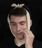 De jongen in een headscarf lijdt van pijnlijke tandpijn Stock Foto