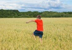 De jongen in een heldere T-shirtlooppas langs het gele gebied waar de oren van korrel, de korrel tegen de blauwe hemel, de achter Stock Foto