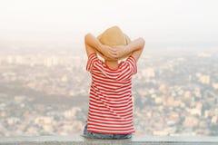De jongen in een hoed zit met zijn handen achter zijn hoofd en bekijkt de stad van een hoogte Achter mening Stock Foto