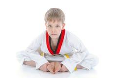 De jongen in een kimono zit op een vloer Stock Fotografie