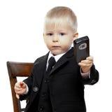 De jongen in een kostuum heeft controle over telefoon Stock Foto's