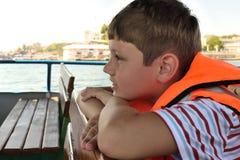 De jongen in een reddingsvest zit op een boot Stock Afbeelding