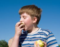 De jongen eet appel Stock Afbeelding
