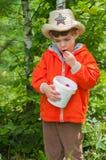 De jongen eet de aardbei Stock Foto
