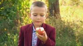 De jongen eet een appel stock footage