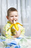 De jongen eet een banaan Stock Foto