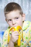 De jongen eet een banaan Stock Afbeeldingen